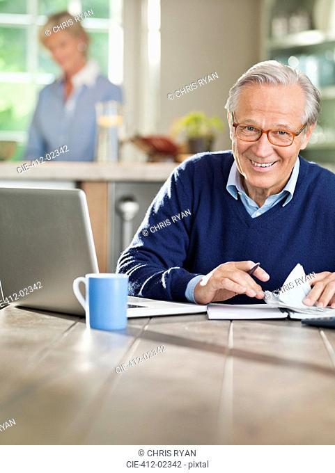 Man using laptop at kitchen table