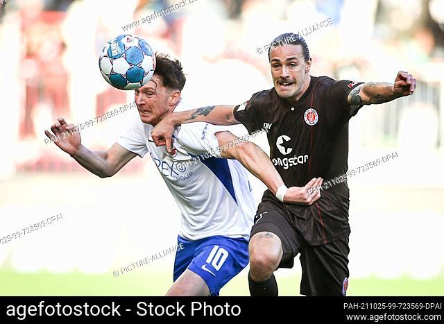 24 October 2021, Hamburg: Football: 2. Bundesliga, Matchday 11, FC St. Pauli - Hansa Rostock at Millerntor-Stadion. St. Pauli's Jackson Irvine (r) and Rostock's...