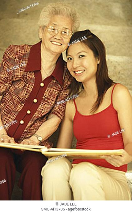 Grandmother with granddaughter, holding picture album
