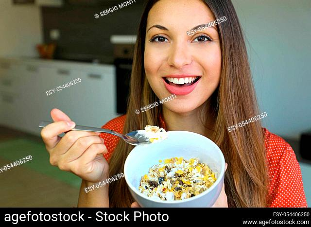 Close up of beautiful young woman eating skyr yogurt with cereal muesli fruit at home, looking at camera, focus on the model eyes, indoor picture