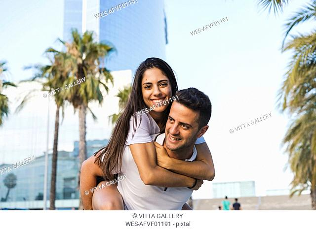 Happy couple in the city, man carrying his girlfriend piggyback