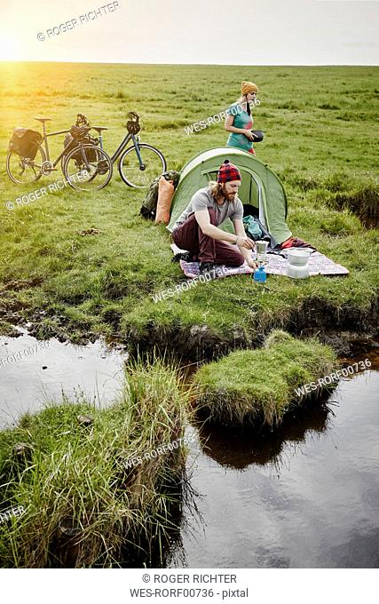 Germany, Schleswig-Holstein, Eiderstedt, couple with bicycles camping in marsh landscape
