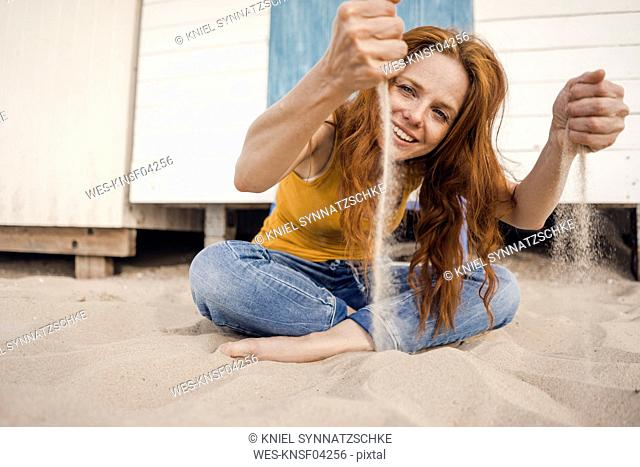 Redheaded woman sitting in front of beach cabin, with sand trickling through her hands