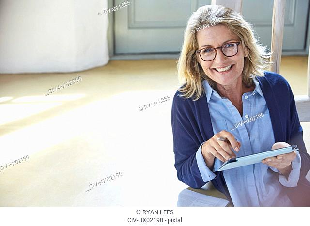 Portrait smiling senior woman using digital tablet