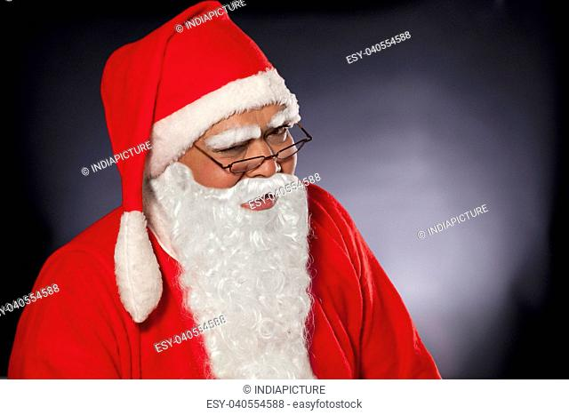 Close up of Santa Claus winking over colored background