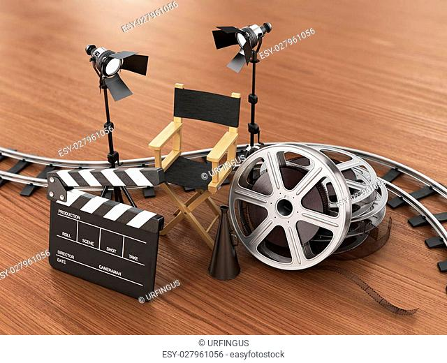 Video, movie, cinema concept. Light, film strip, reels, rails, clapperboard and director chair on the wood background