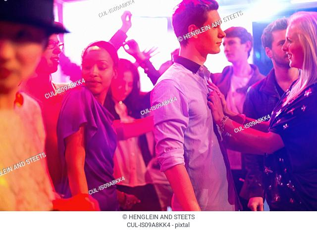 Teenage girl with hands on boy's chest at party