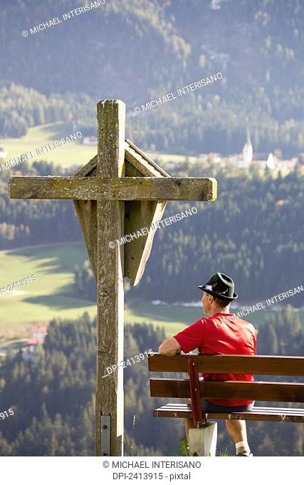 Male hiker sitting on bench with large wooden cross overlooking valley with gren meadows and trees; Aschau, Austria