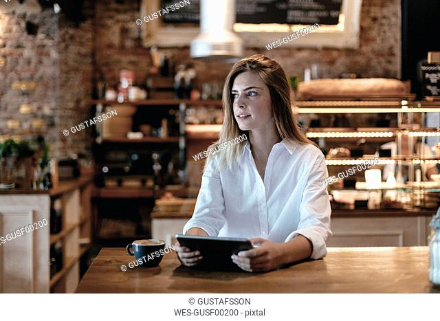 Blond woman sitting in cafe, using tablet, thinking
