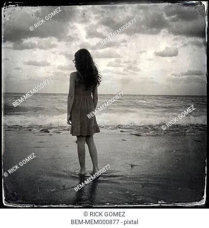 Hispanic woman walking on beach