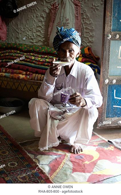 Turbanned man sipping tea from saucer in tribal home in front of piles of hand embroidered quilts, Soyla, Kachchh, Gujarat, India, Asia