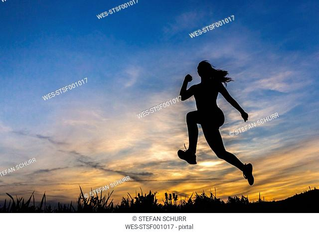 Silhouette of female jogger at sunset