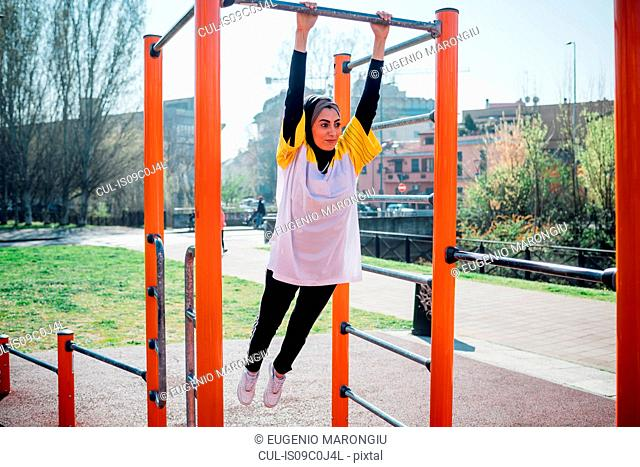 Calisthenics class at outdoor gym, young woman swinging from exercise equipment