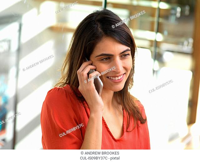 Woman using mobile phone in office