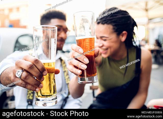 Happy young couple clinking beer glasses outdoors at a bar