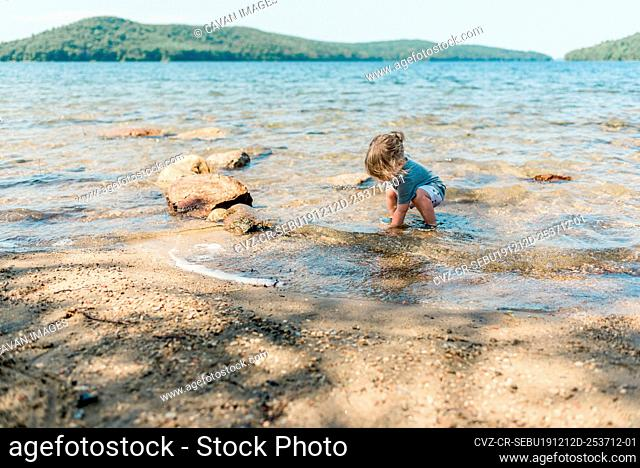 Little toddler girl playing in a lake