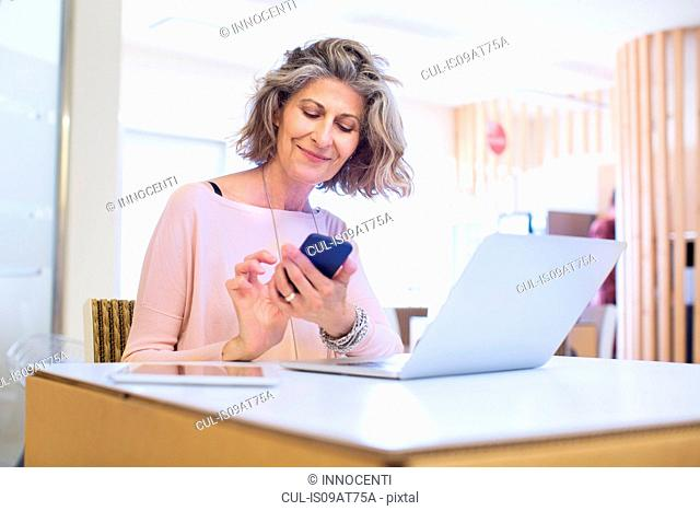 Portrait of senior female designer texting on smartphone in office