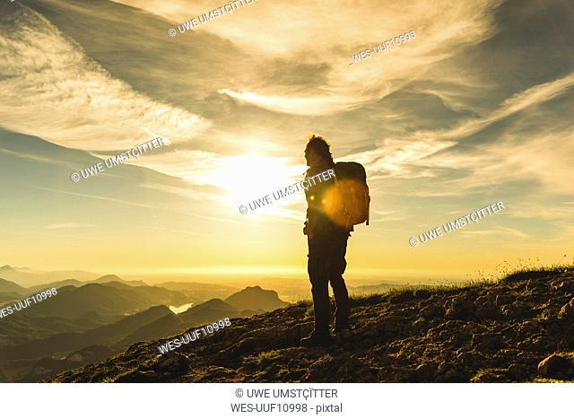 Austria, Salzkammergut, Hiker standing on summit, looking at view