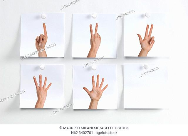 Five white Post It hanging on the wall with images of fingers indicating numbers and an empty one