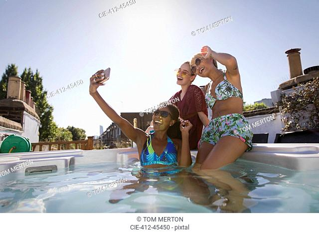 Happy, carefree young women friends in bikinis taking selfie with camera phone in sunny, rooftop hot tub