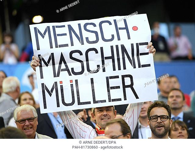 "German fan holds a sign """"Mensch Maschine Müller"""" during the UEFA EURO 2016 quarter final soccer match between Germany and Italy at the Stade de Bordeaux in..."