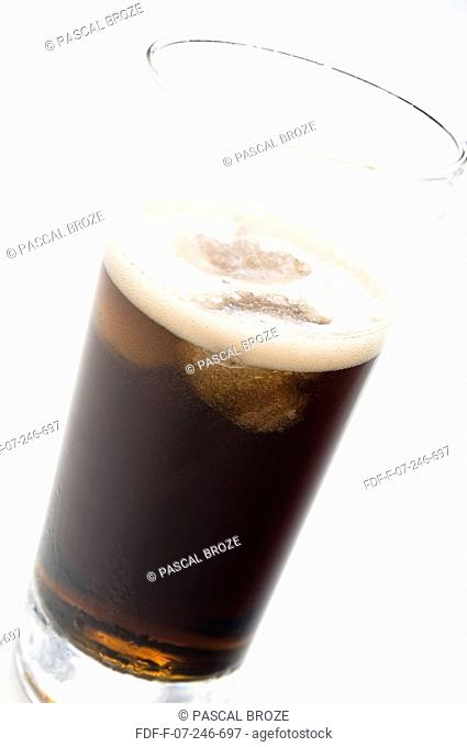 Close-up of a glass of cola with ice cubes