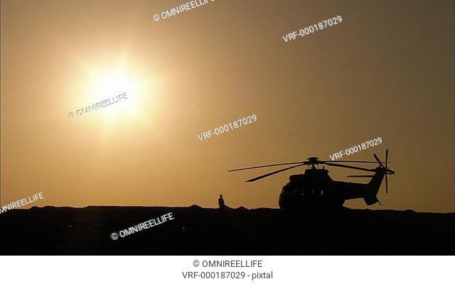 Helicopter and human silhouette with sun behind