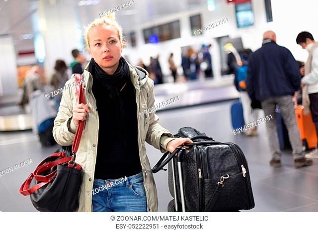 Casually dressed young female traveller walking in airport terminal hall with collected laggage after flight arrival . Blured background