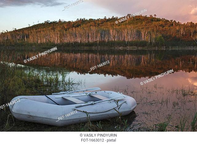 Empty inflatable raft moored on lakeshore against forest, Svobodniy, Amur, Russia