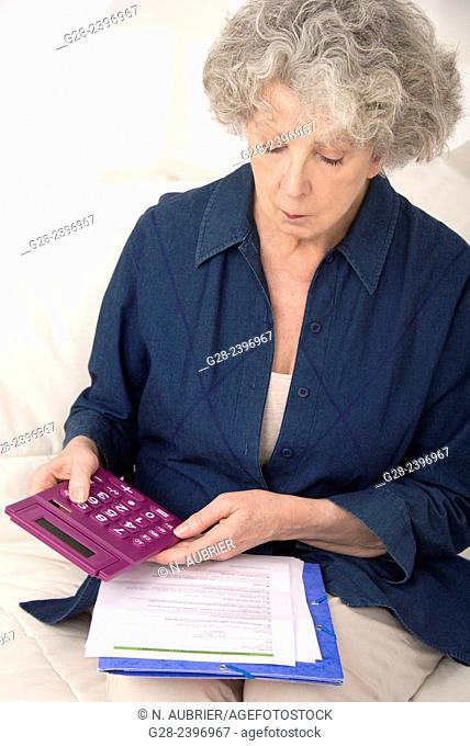 Beautiful senior woman holding a pocket calculator and reading papers at home