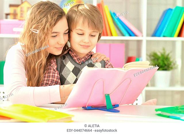 Teenage girl helping her little brother with homework