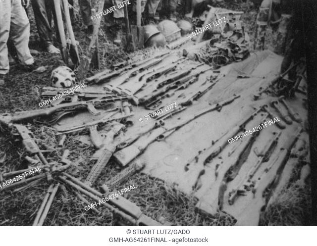 Captured Viet Cong weapons, including rifles and other small arms, laid out on a blanket, the legs of a group of soldiers visible standing around the captured...