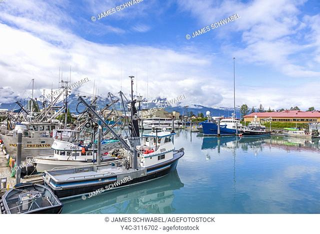 Big white clouds with patches of blue sky over small boat harbor on Prince William Sound in Valdez Alaska