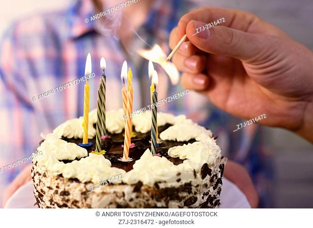 male hand lights the candles on the birthday cake
