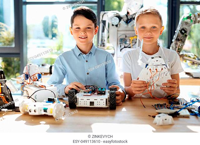 Our creations. Charming preteen boys sitting at the table full of robots and showing their own works robotic vehicle and a robot-warrior