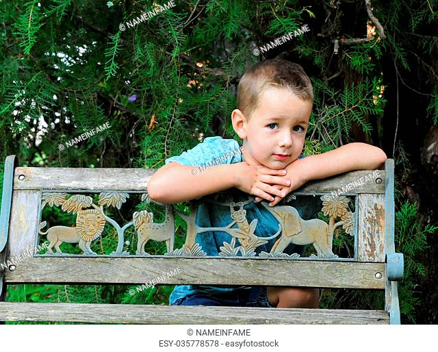 No one knows a childs thoughts behind his eyes. This young boy leans against a wooden park bench and considers the problems of his young world