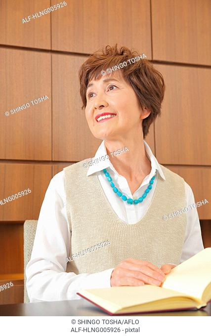 Fashionable Japanese senior woman reading book