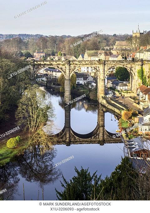 The railway viaduct reflected in the River Nidd on a sunny winter day at Knaresborough North Yorkshire England