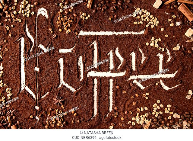 Calligraphic inscription gothic letters coffee over ground black coffee scattered on white marble with roasted and unroasted beans, cinnamon, sugar