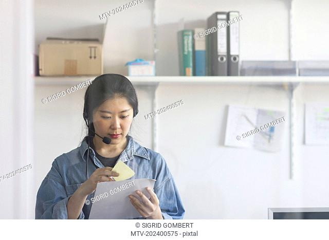 Young female engineer wearing headset and working in an industrial plant, Freiburg im Breisgau, Baden-Württemberg, Germany