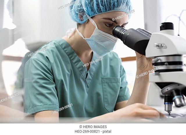 Female medical technician using microscope in laboratory