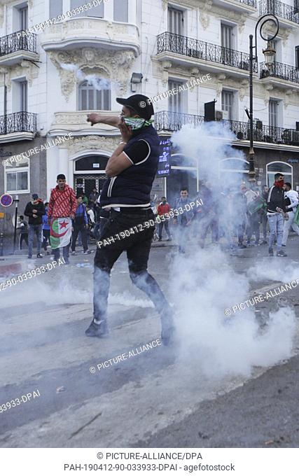 12 April 2019, Algeria, Algiers: An Algerian protester throws back a tear gas canister fired by Algerian security forces during clashes that followed an...