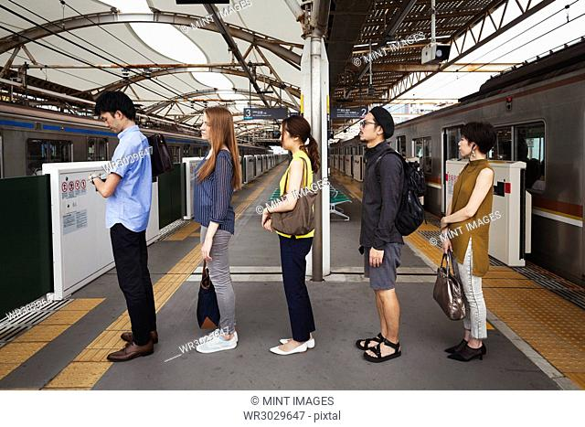 Five people standing in a row on a subway platform, waiting in line, Tokyo commuters