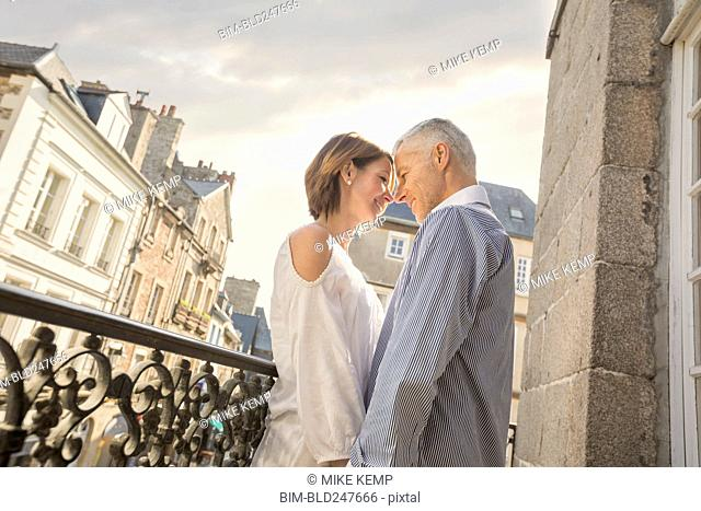 Caucasian couple rubbing your noses on balcony in city