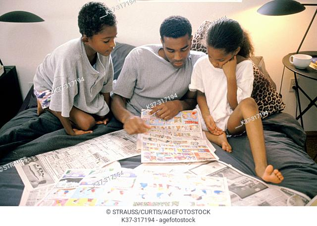 African-American father and children reading newspaper's comics