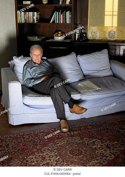 Senior man sitting on sofa watching television