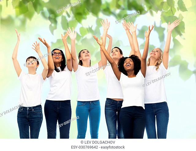 diversity, ecology and people concept - international group of happy smiling volunteer women in white blank t-shirts having fun over green natural background