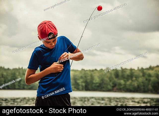 Close up of teen boy with a fish on his rod on a lake in the summer