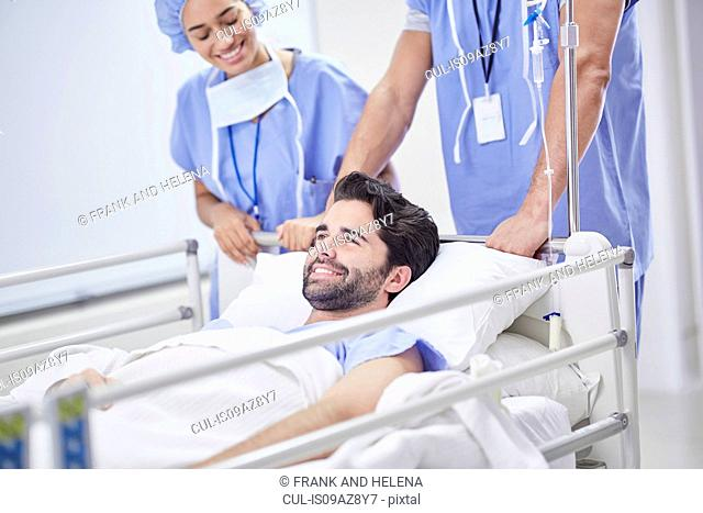 Doctors pushing smiling patient in hospital bed
