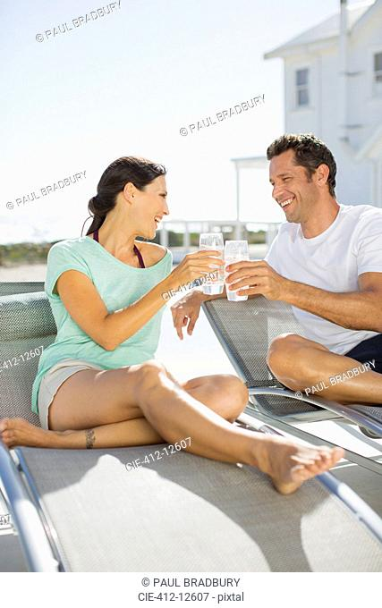 Couple toasting glasses on lounge chairs